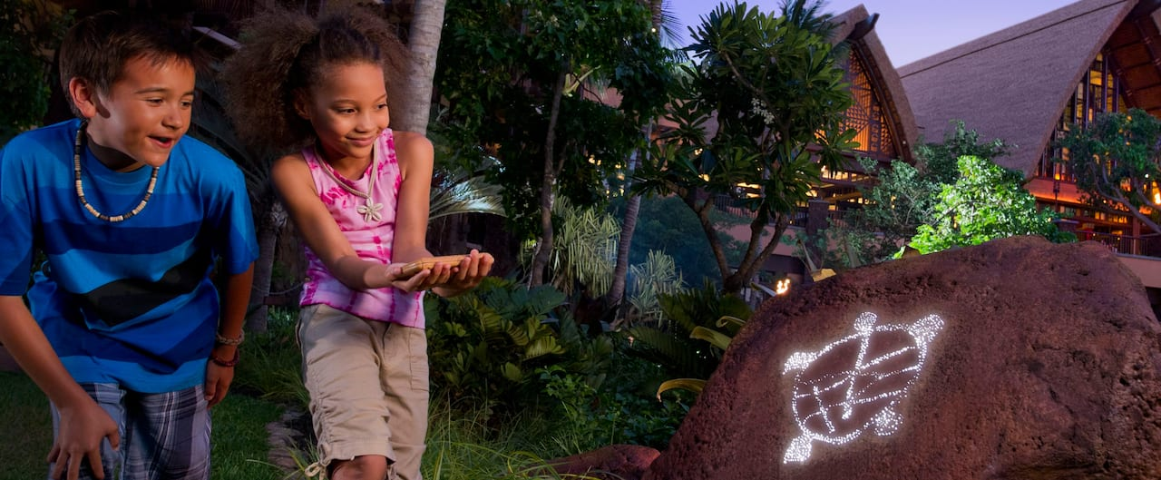 A young boy and girl discover a turtle symbol on a rock on the Menehune Adventure Trail