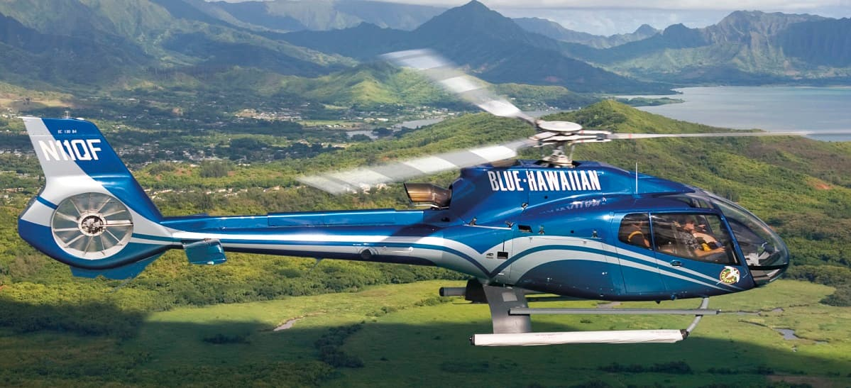 The Blue Hawaiian helicopter flies over a lush valley on O'ahu as it heads towards the shoreline