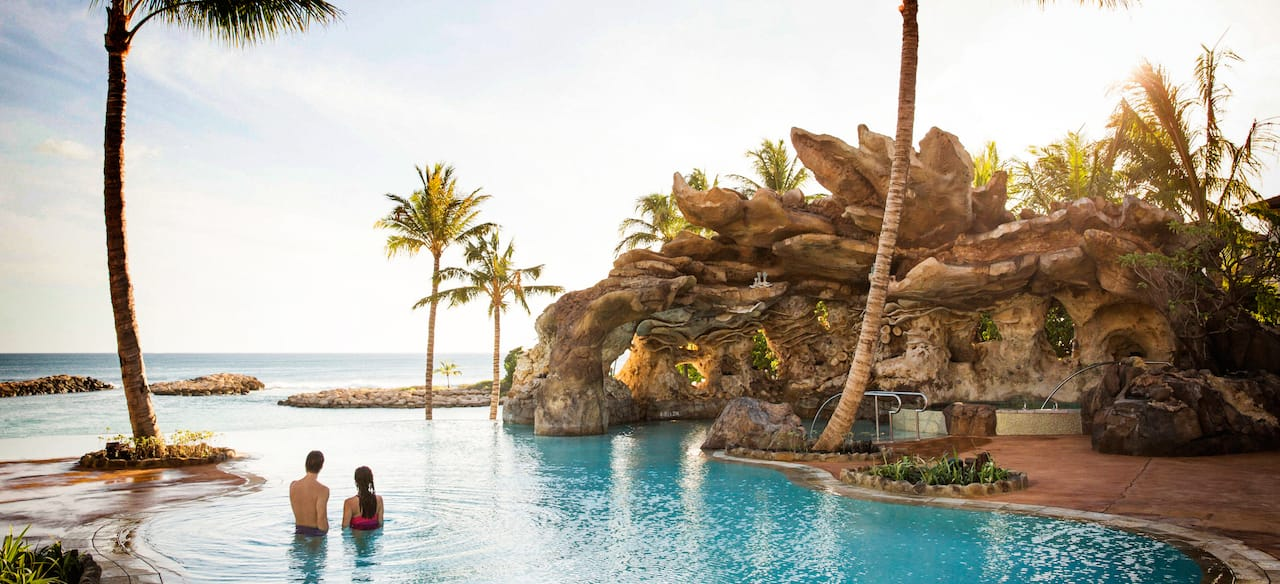 A couple unwinds in the waters of the Ka Maka Grotto oceanfront pool while looking out to the ocean