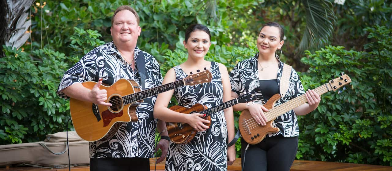 The musical trio Kapena, one man holding a guitar and two women, both holding their instruments, stand amid the Aulani foliage wearing matching Hawaiian print outfits