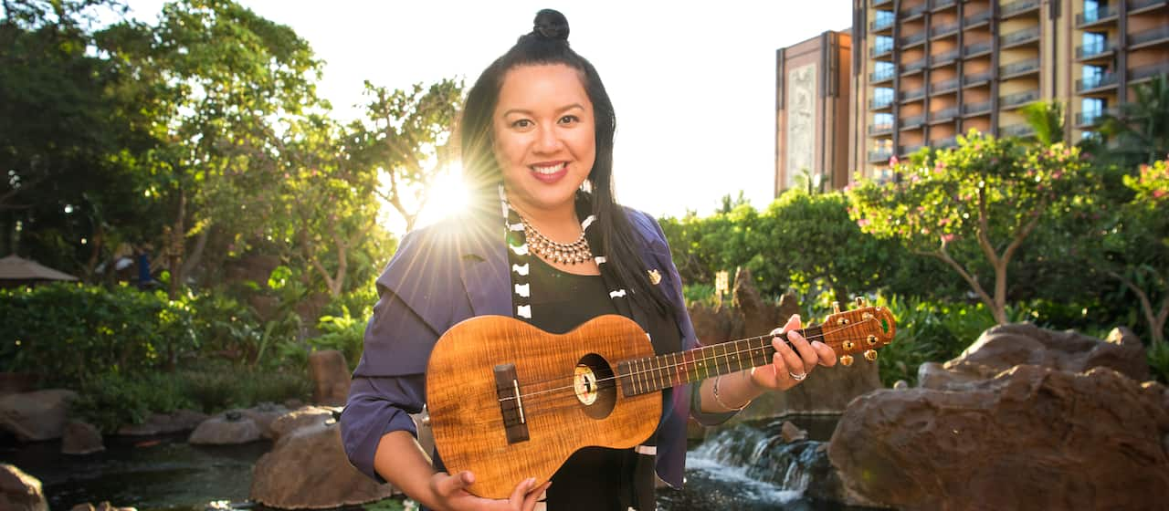 Mailani poses with her 'ukulele in front of a koi pond at Aulani Resort