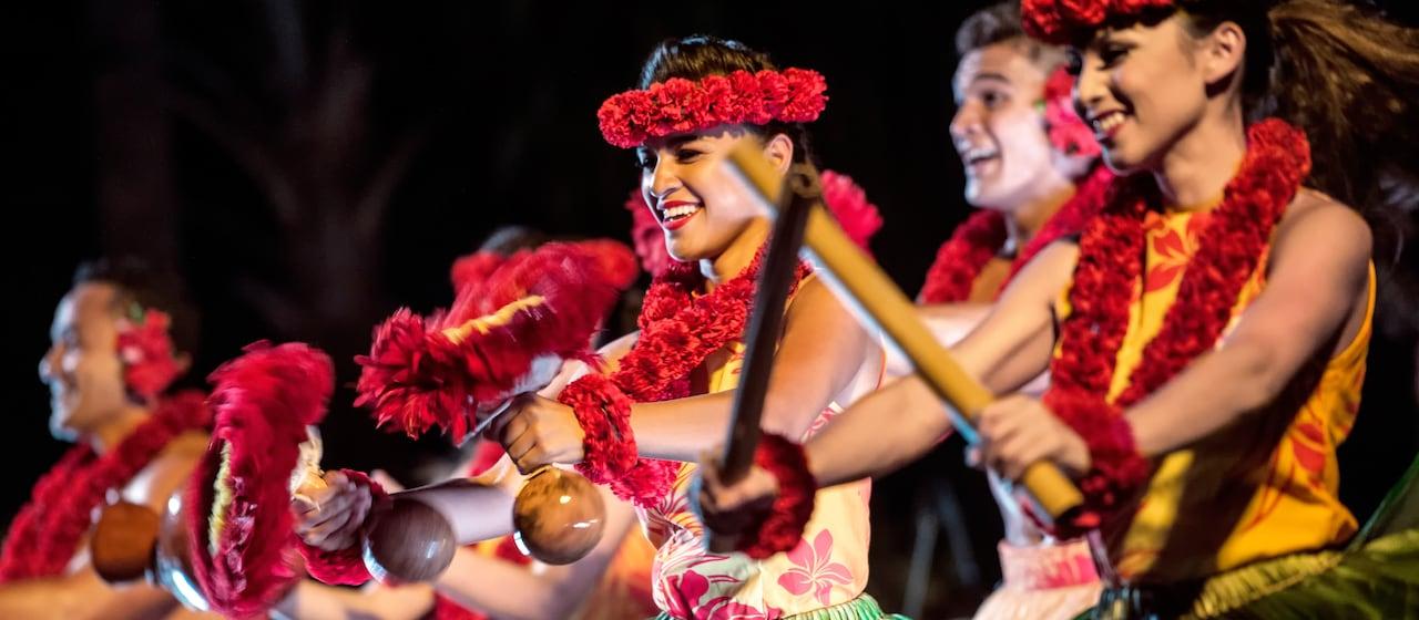 やしの葉でできたスカート、レイ、ヘッドドレスを身に着けて、竹やココナツ、花を使ったハワイの伝統的な楽器を演奏するハワイアン・ダンサーたち。