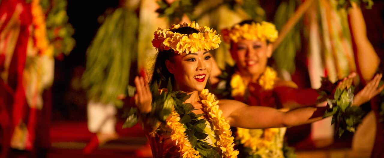 Two female hula dancers performing in traditional Hawaiian dress with floral leis and headbands
