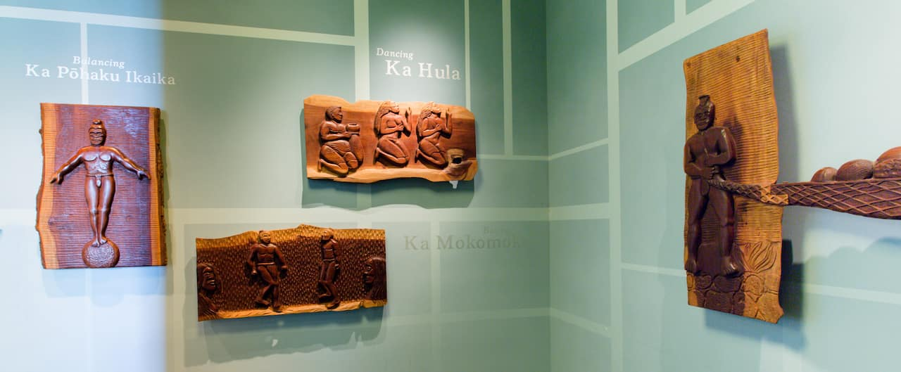 Wood relief carvings of natives engaged in various activities