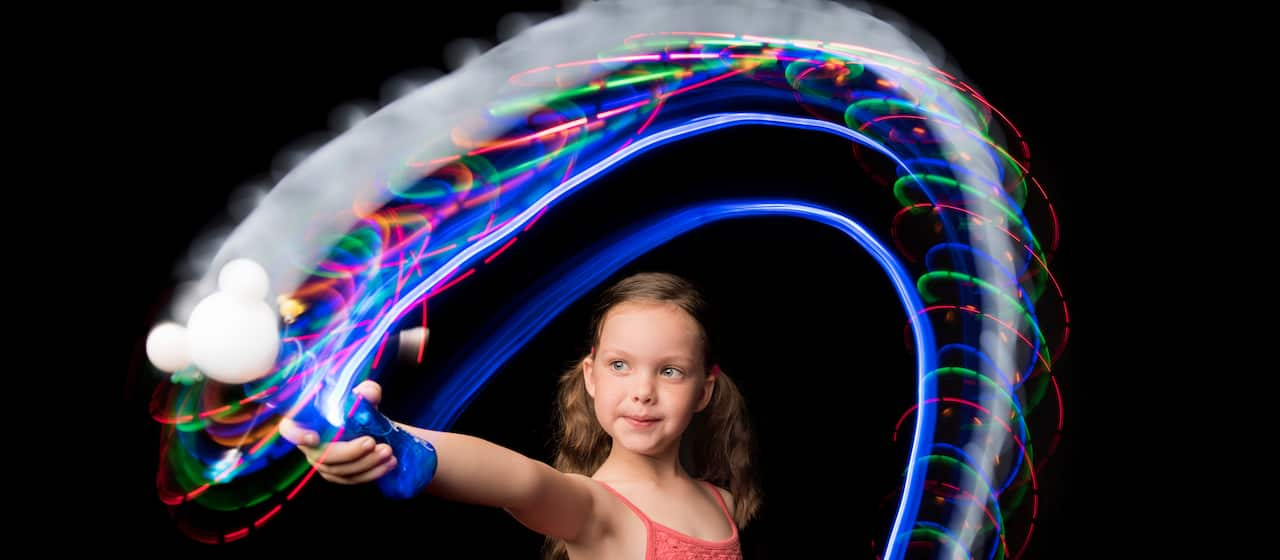 A young girl waves a Mickey Mouse light wand that creates a trail of lights behind it