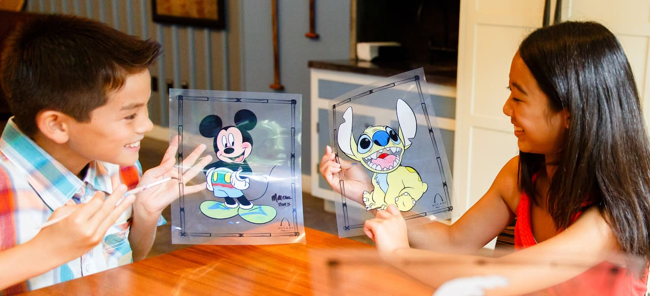 A boy and a girl show each other Disney character animation cels they have painted