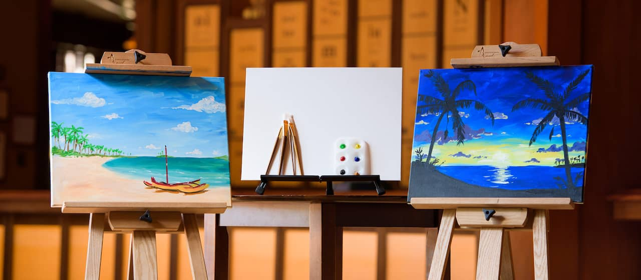 Two painted canvases on easels are on either side of a blank canvas with paint brushes and paints