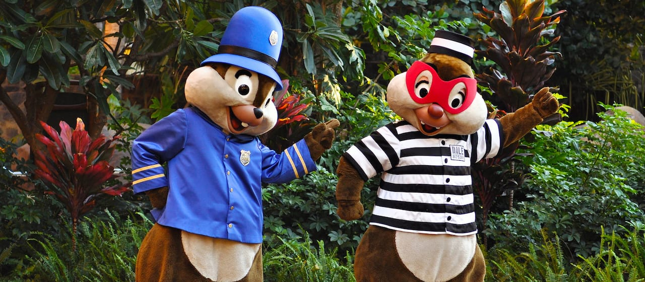 Chip, dressed as a policeman, stands beside Dale, who is dressed in a striped convict costume with a mask