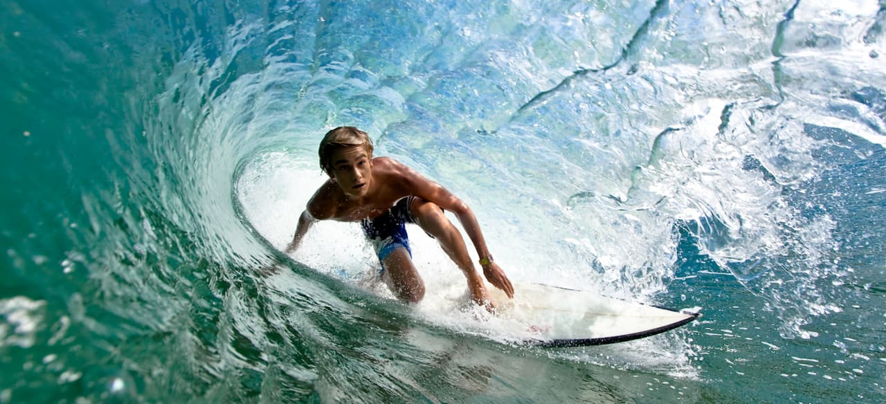 A teen boy rides a surfboard inside the barrel of a large wave