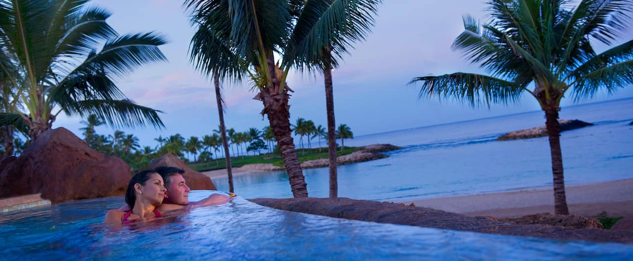 A mature couple leans toward one another in a whirlpool spa while gazing at the ocean
