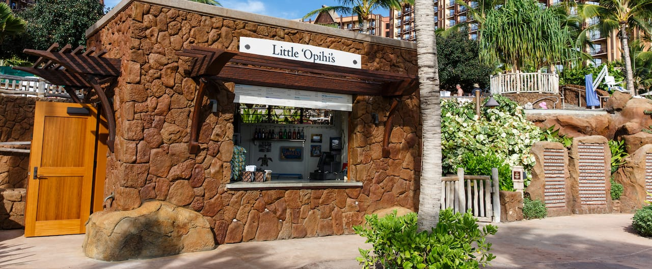 The exterior of Little 'Opihi's, a rectangular, stone shack with a quick service window