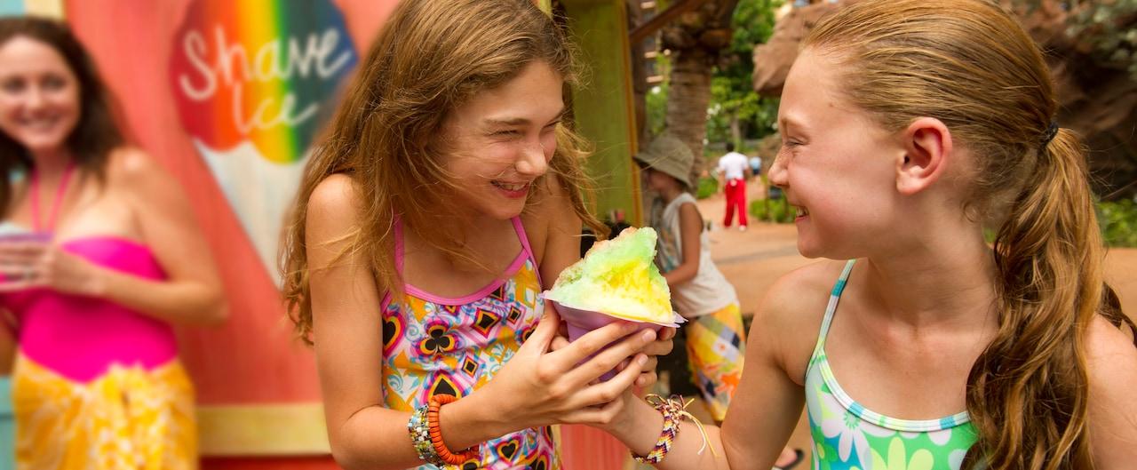 シェイブ・アイスを持って笑い合う水着を着た 2 人の少女と、シェイブ・アイスを手に少女たちを見ている女性