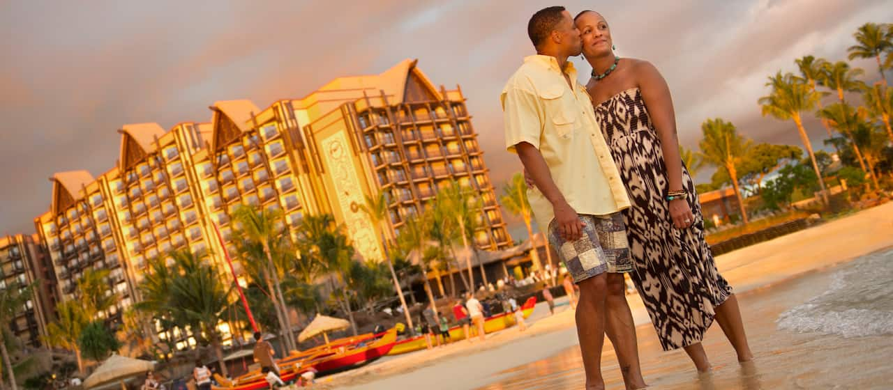 A man kisses a woman on the cheek as they stand on the shore in front of Aulani Resort