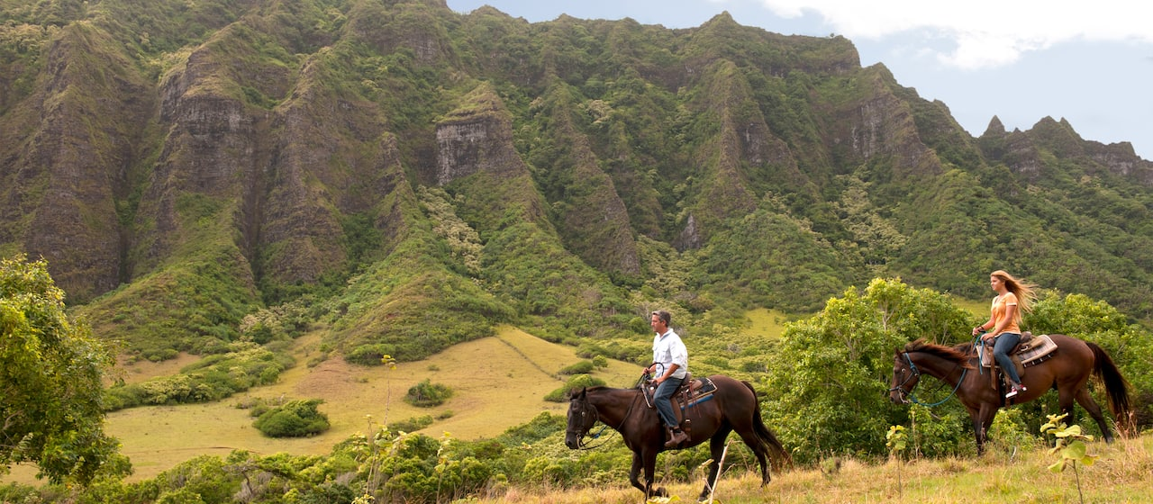 A man and a woman ride on horseback through a Hawaiian valley