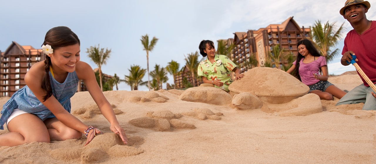 Two teen girls sculpt large and small 3D turtles in the sand under the direction of a Cast Member