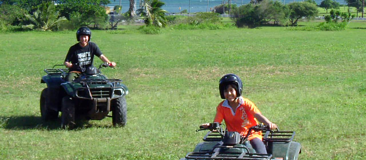 A teen boy and teen girl riding all terrain vehicles across a field