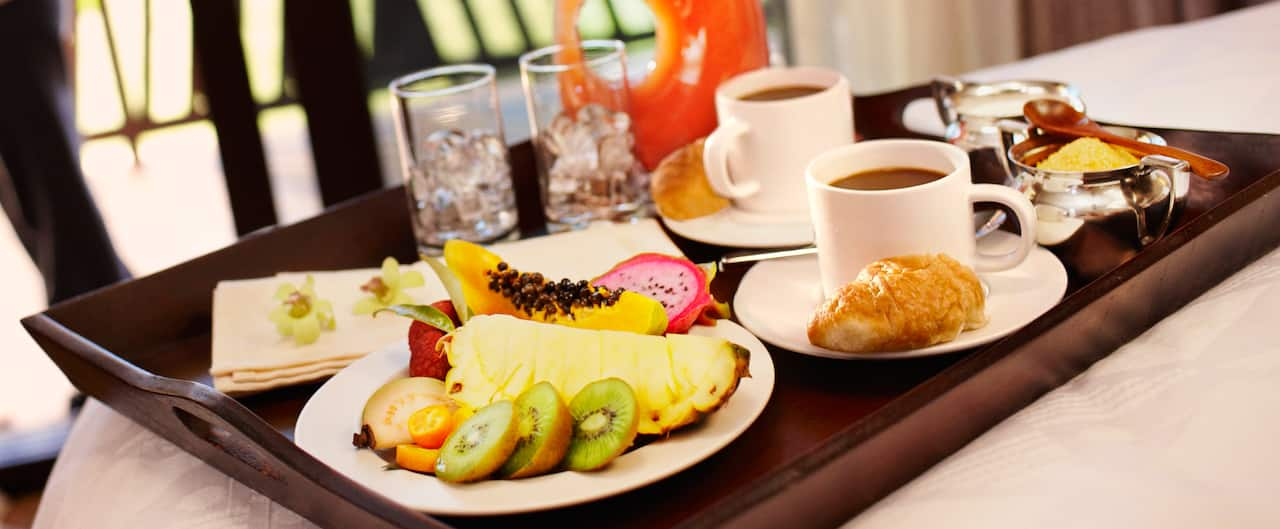A tray with a pitcher of juice, glasses, cups of coffee a croissant and fresh fruit