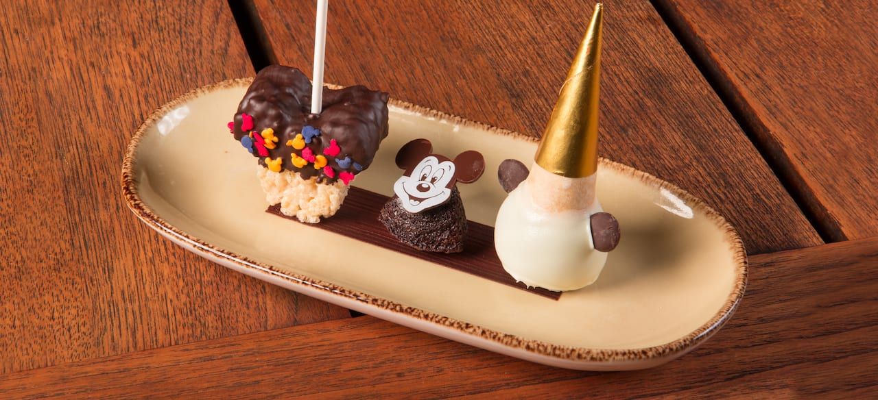 A crispy rice treat, a brownie and an ice-cream cone-shaped confection are presented on a platter.