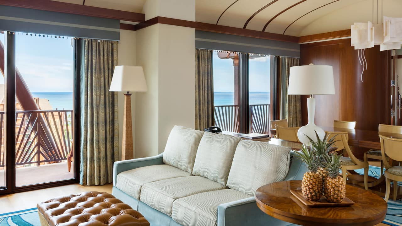The living area of the Deluxe 1-Bedroom suite has a plush couch and a dining table with chairs