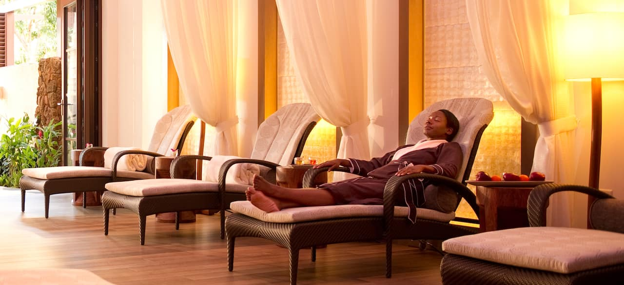 A woman in a spa robe relaxes in a lounge chair along a wall with white drapes and more lounge chairs