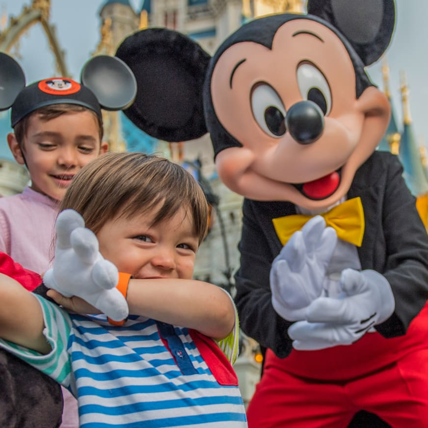 A young boy and his family share a moment with Mickey Mouse
