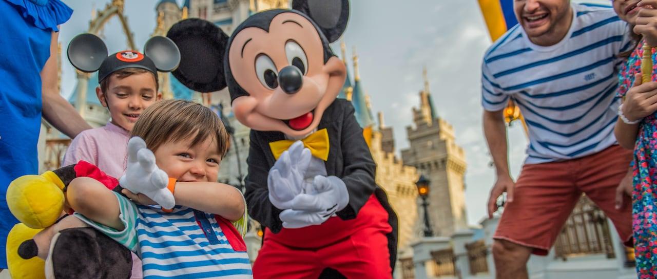 Un jeune garçon sourit et sa famille partage un moment avec Mickey Mouse