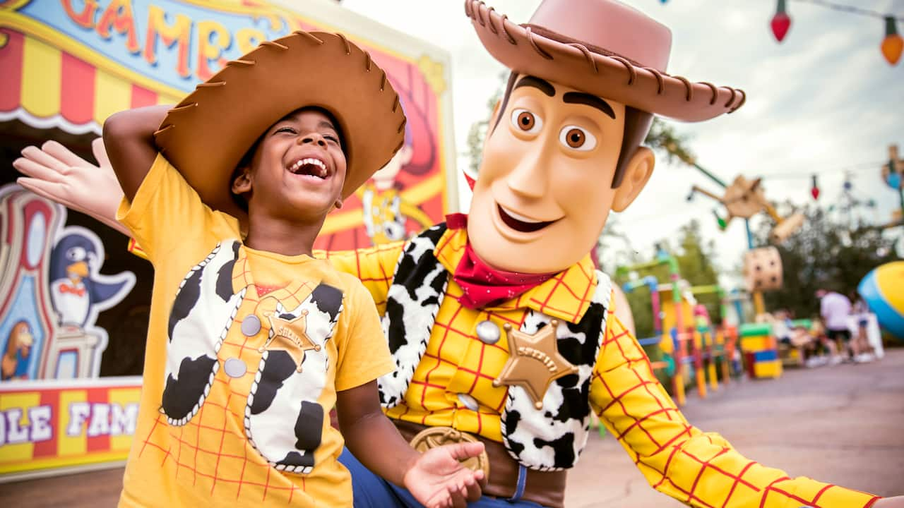 A young Guest dressed as Woody enjoys a laugh with Woody in Toy Story Land at Disney's Hollywood Studios