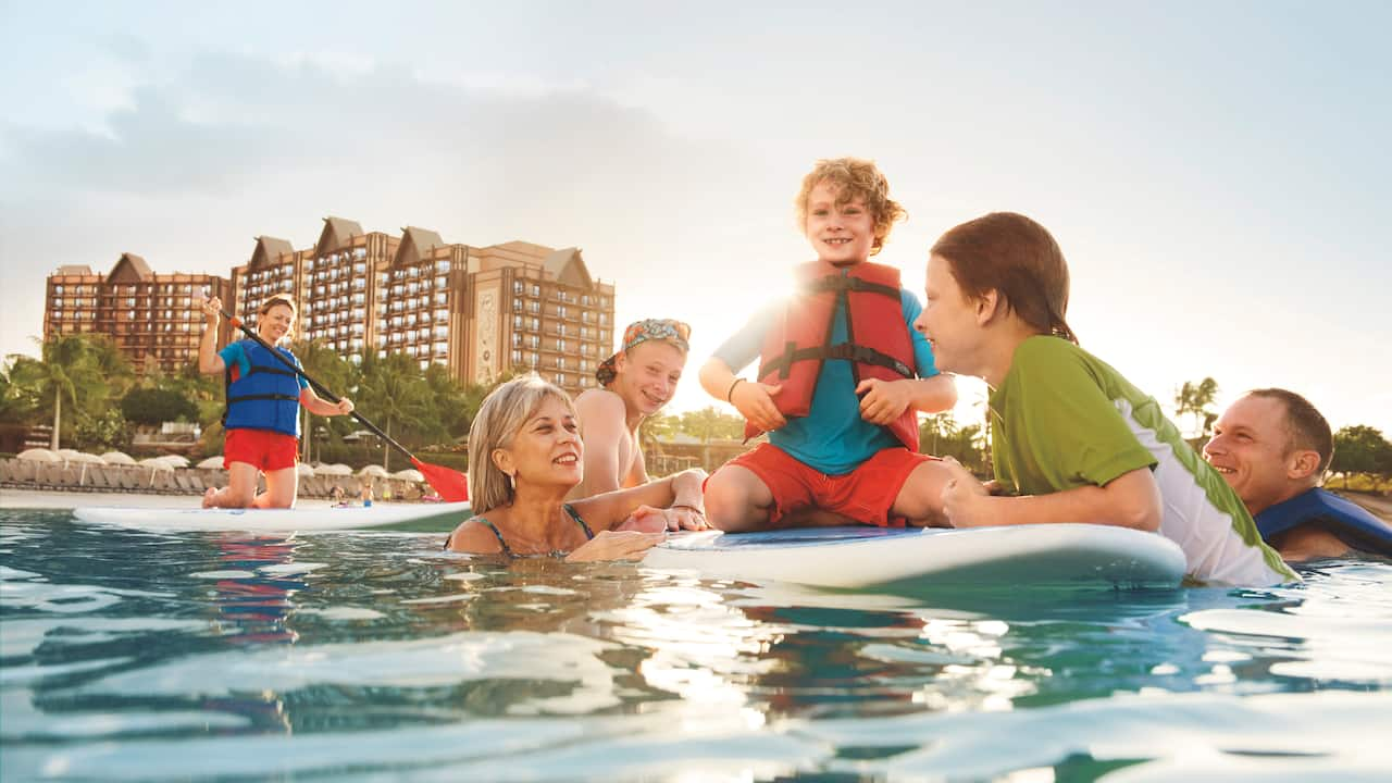 At Aulani Resort, a girl paddles on a surfboard toward her mother, 2 brothers and sister