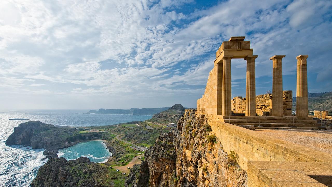Des ruines antiques avec des colonnes au sommet de l'Acropole surplombant la baie de Saint-Paul en forme de cœur et la mer Égée