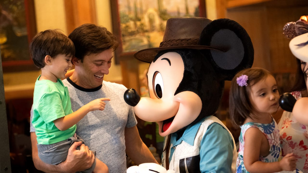 Mickey Mouse, dressed as an explorer, interacts with Guests