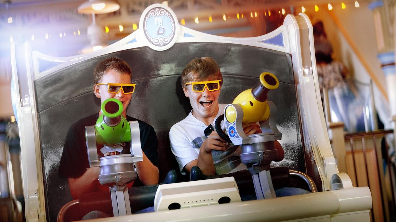 Dos niños usan sus disparadores de resorte en Toy Story Mania!