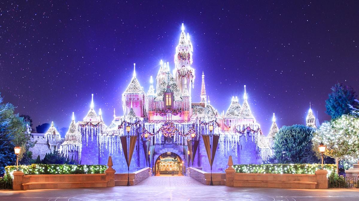 El Castillo de la Bella Durmiente iluminado con luces festivas y decorado con una guirnalda y corona