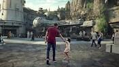 Papá e hija caminan mano en mano hacia la tierra Star Wars: Galaxy's Edge, en Disneyland Resort