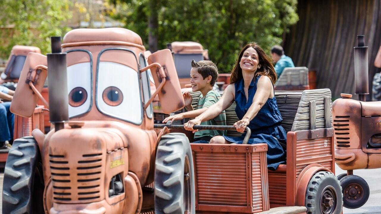 Una mamá pasea con su hijo en remolque, en la atracción Mater's Junkyard Jamboree