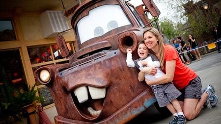 Una mamá arrodillada con su pequeño hijo en brazos, junto a una réplica de la grúa Tow Mater