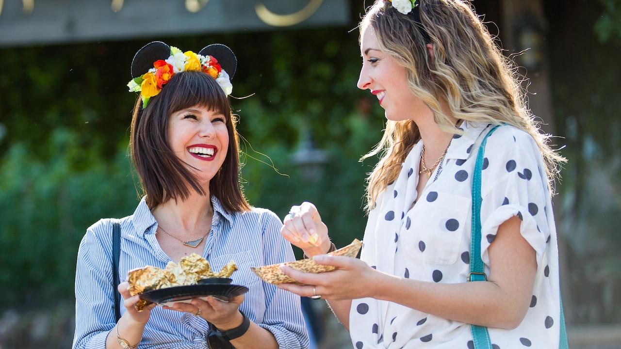 Dos mujeres ríen mientras disfrutan la comida de un Festival Marketplace