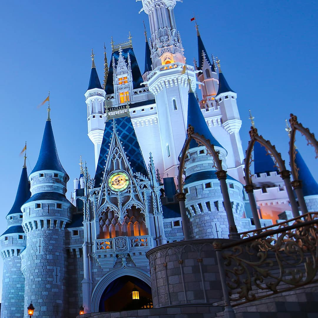 At dusk, lights shine from the windows of Cinderella Castle at Walt Disney World Resort