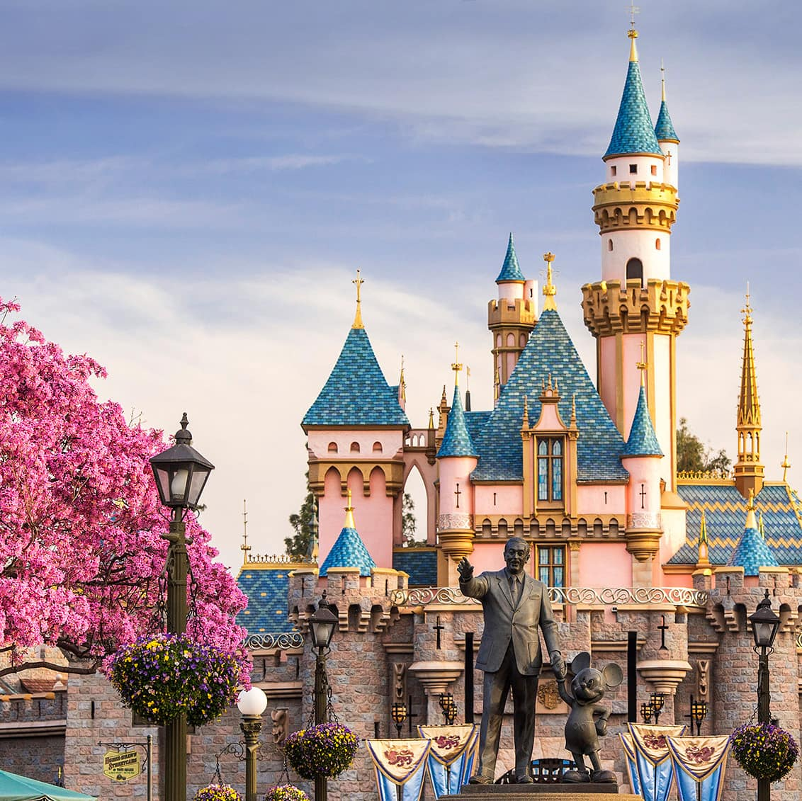 Flowering trees flank the Partners Statue of Walt Disney and Mickey Mouse and Sleeping Beauty Castle