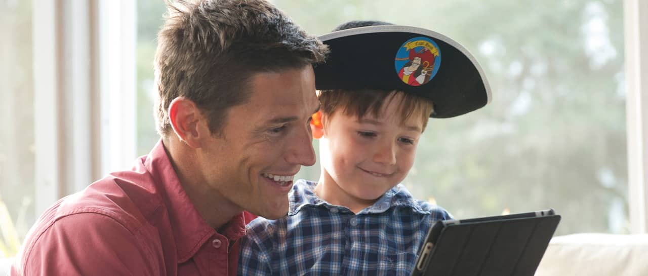 A man and a little boy wearing a pirate hat look at an electric tablet
