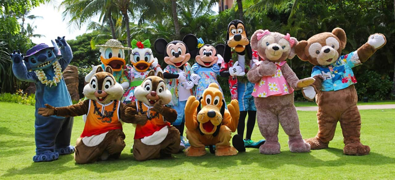 A group shot of 11 Disney Characters, including Mickey, Minnie, Pluto and Stitch, in front of palm trees