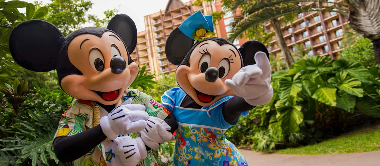 Mickey and Minnie dressed in Hawaiian clothes standing on a walkway