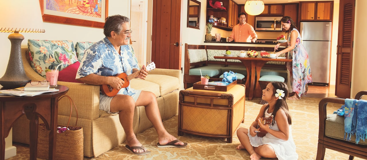 A grandfather and granddaughter play ukuleles while mom and dad prepare food in the kitchen and dining area