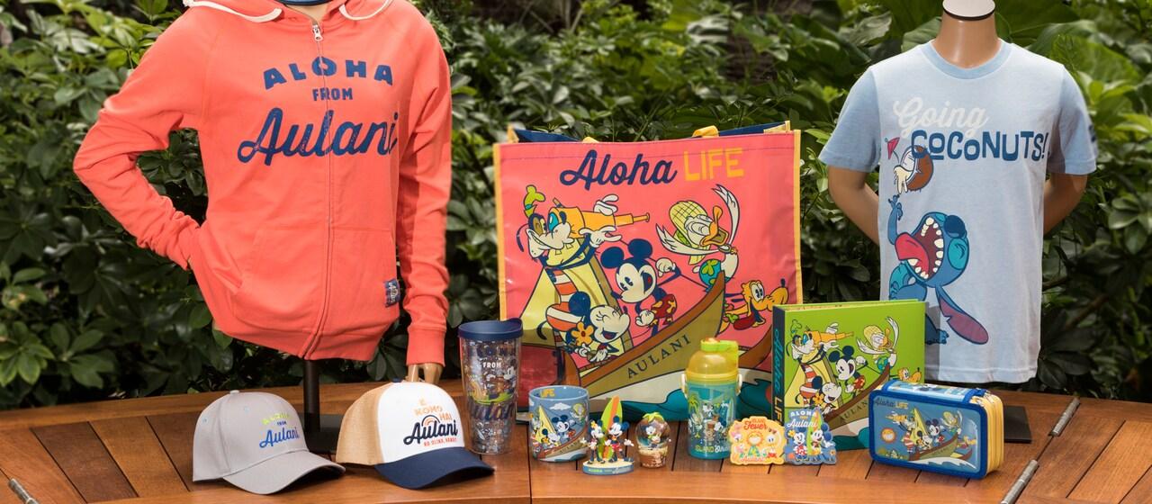 緑豊かな背景の前に並べられた、トレーナーや帽子、ミッキーの描かれたバッグ、スティッチの描かれたTシャツ、ポーチなどの魅力的な新商品