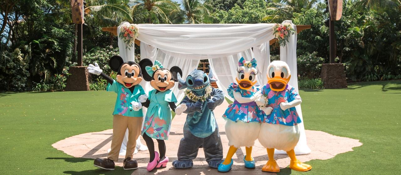 美しいキプカ・ローンで、白い布と花で飾られた結婚式の祭壇とキャノピーの前に立つ、ハワイの衣装を着たミッキーマウス、ミニーマウス、スティッチ、デイジーダック、ドナルドダック