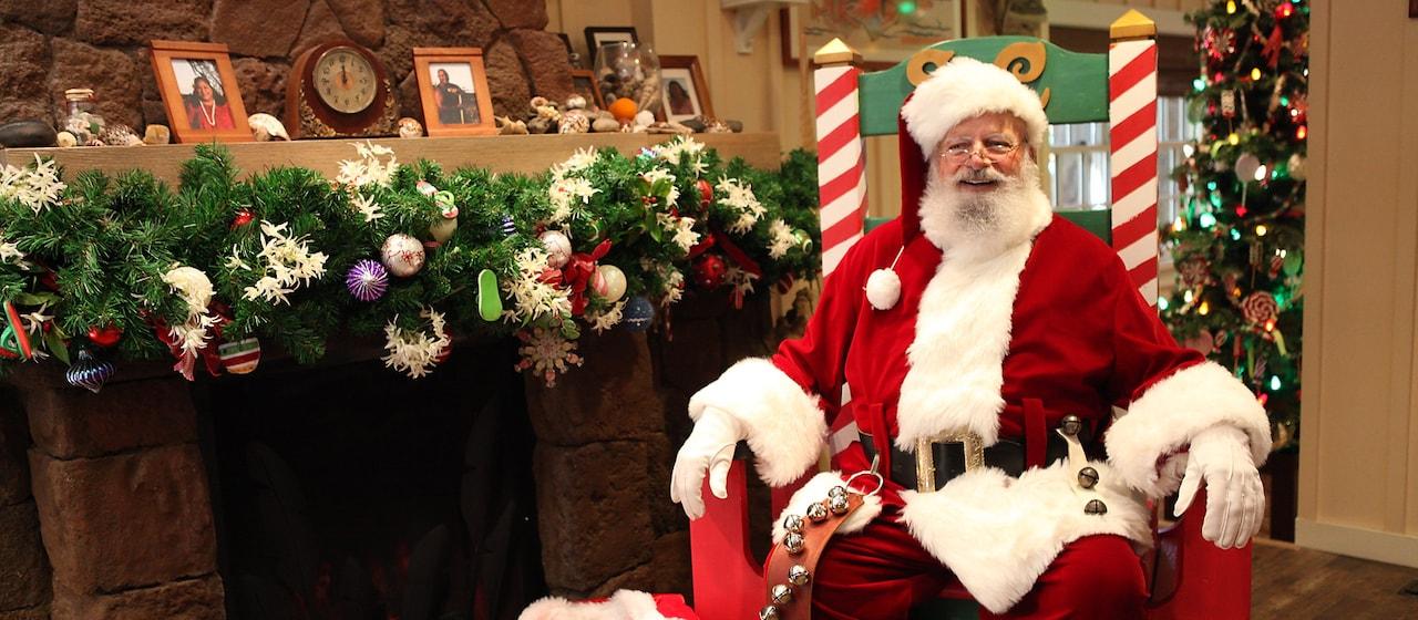 クリスマスカラーの大きな椅子に座るサンタ
