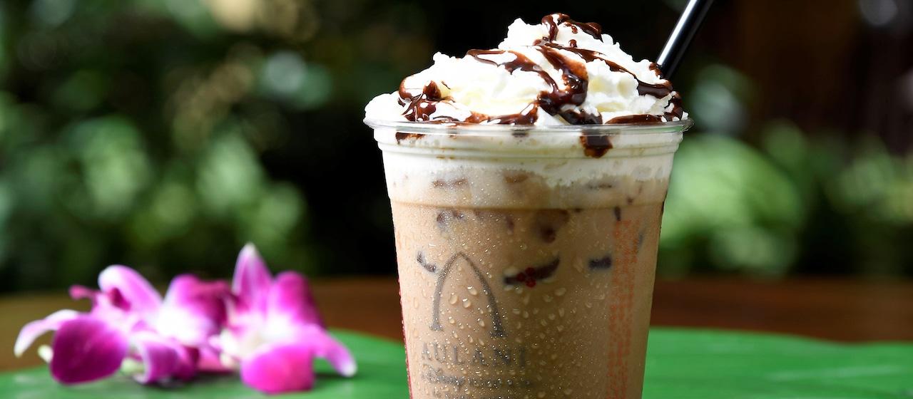 葉っぱの上に置かれたアウラニのロゴ入りプラスチックカップに入ったホイップクリームとチョコレートシロップのトッピング付きフローズン・コーヒー・ドリンクとハイビスカスの花