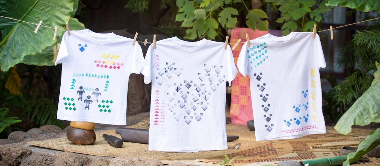 洗濯ばさみでつるされた、カパ・スタンプのデザインが施された 3 枚の T シャツ
