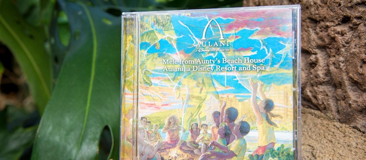 木の側に立てかけられているアウラ二のロゴ付きの、キャンプファイヤーを囲む子供たちの絵が描かれているメレフロムアンティーズビーチハウスアウラ二ディズニーリゾートアンドスパのCD