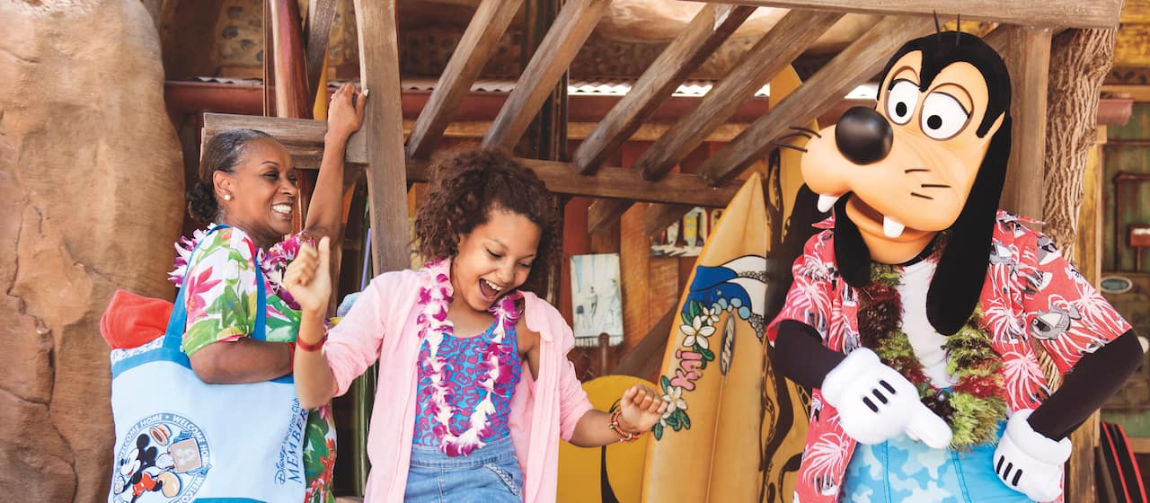 A teenage girl and Goofy, both wearing beach clothes and leis, dancing amidst surfboards in an indoor/outdoor beach location