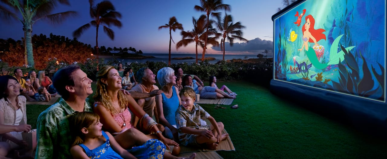 Families watching a Disney movie outside by the ocean